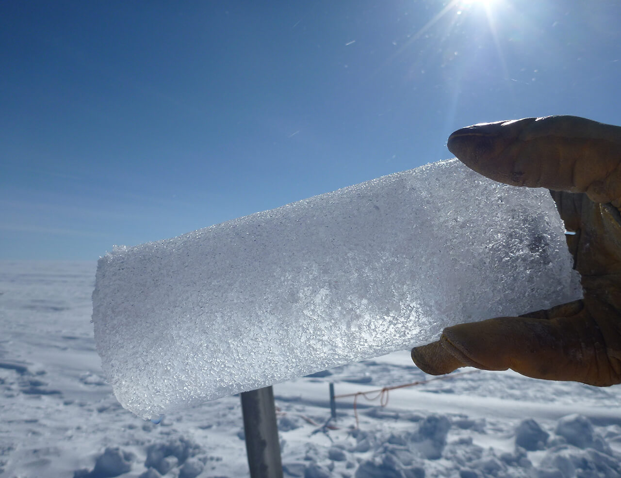 Photograph of a hand holding an ice core.
