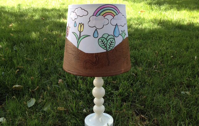 A garden lampshade lamp on the grass.