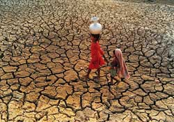 Two girls walking across dry, cracked land, one carrying a jug on her head.