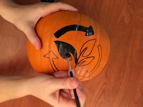 a paintbrush with black paint is being used to fill in the carbon cycle shape on a pumpkin
