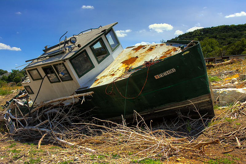 Photo of a boat in dried out lake bed.
