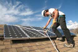 Worker installing solar panel on a roof.