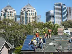 Six people work on roof of house, with tall city buildings in background.